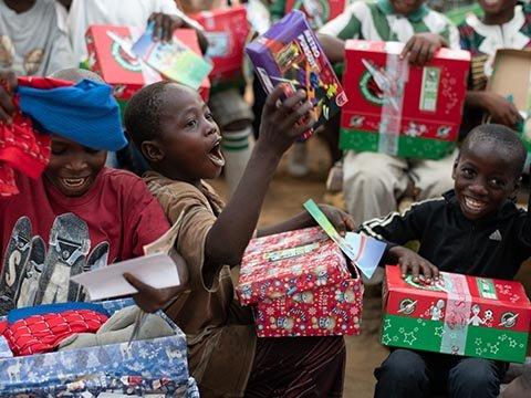 boy shouts with joy while exploring shoebox gift