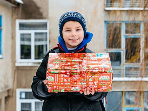 Boy outside smiles with shoebox gift