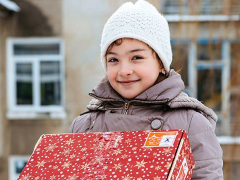 girl in hat, smiles with shoebox gift