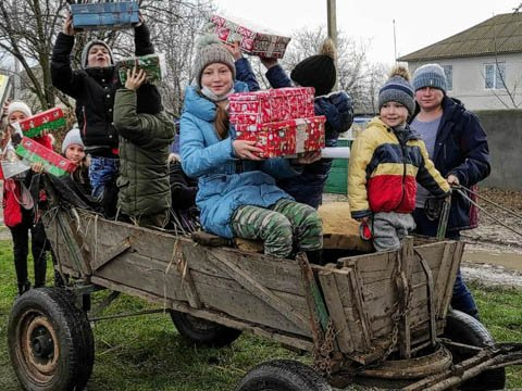 family on cart with shoebox gifts