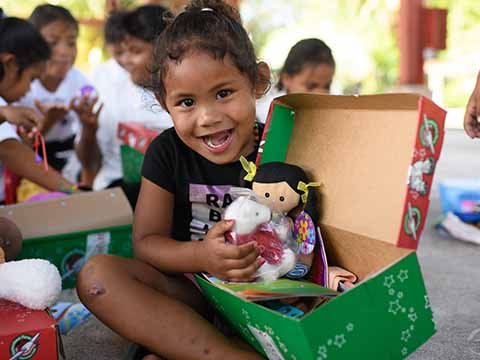 young girl smiles as she explores her shoebox gift