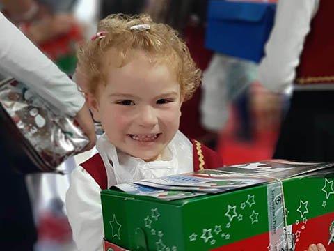 girl with shoebox smiles