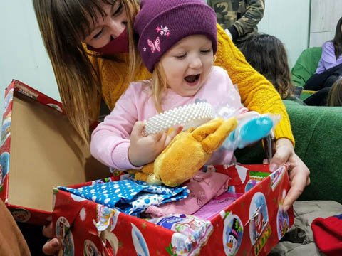 girl explores shoebox gift excitedly