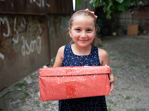 Girl smiles with red sparkly shoebox