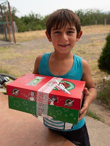 Boy in Georgia holding shoebox gift
