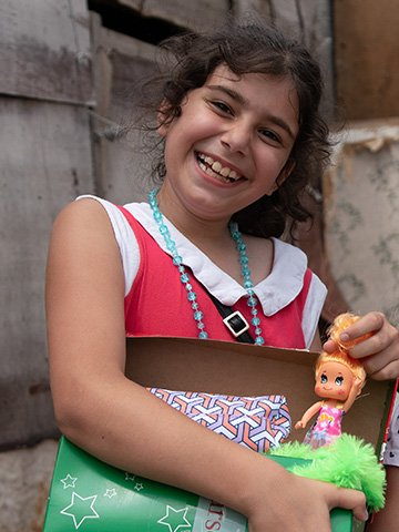 Girl grinning with shoebox gift