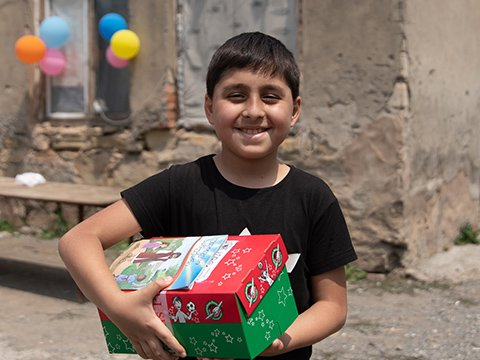 boy smiles with red and green shoebox