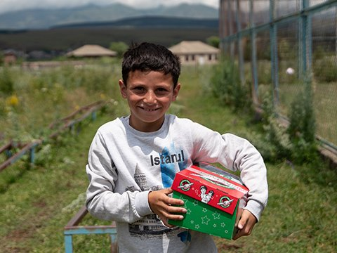 Boy in Georgia holding red and green shoebox gift