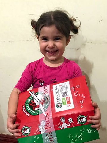 girl beams with red shoebox