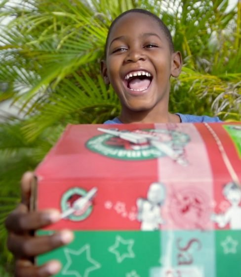 Child smiles with shoebox gift
