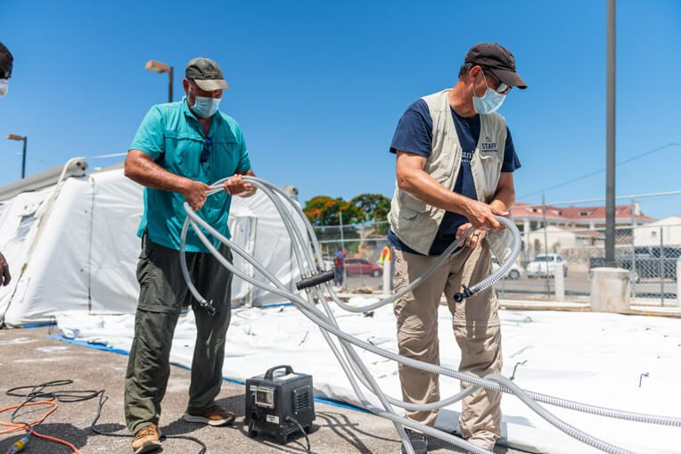 Our team is preparing a tent for construction and for air conditioning and electricity. This is the second COVID-19 response for Mark Randolph, left, to the island nation.