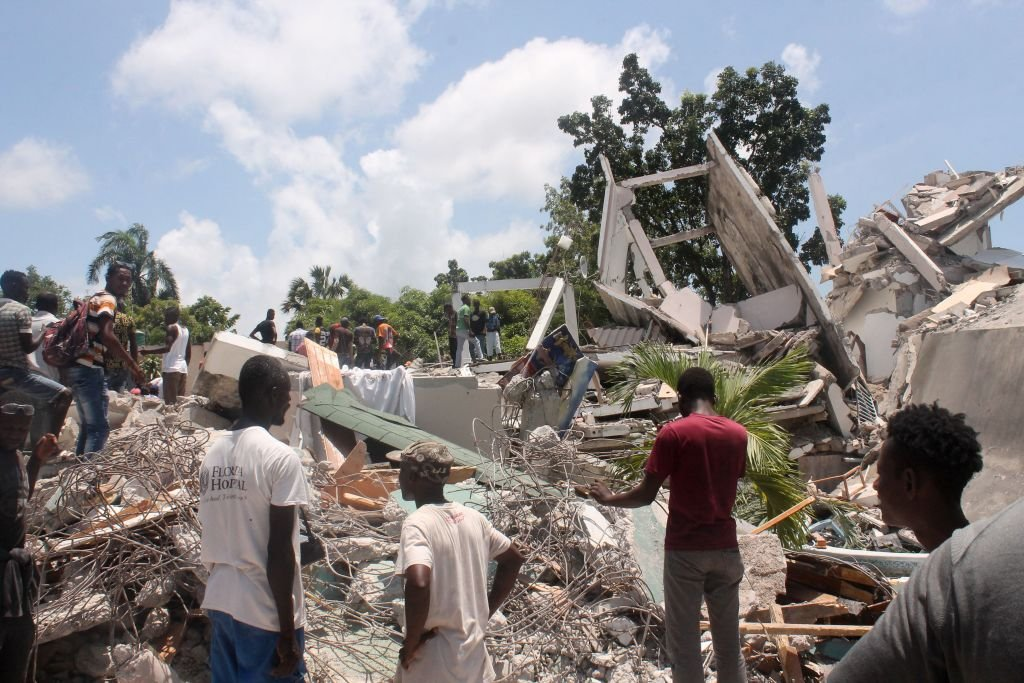 People search through the rubble of what used to be the Manguier Hotel after the earthquake hit on 14 August 2021 in Les Cayes, southwest Haiti. - (Photo by Stanley LOUIS / AFP) (Photo by STANLEY LOUIS/AFP via Getty Images)