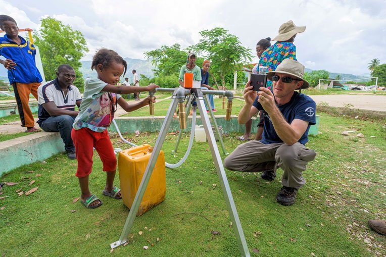 Dano's daughter collects water from the new tap stand installed by Samaritan's Purse.